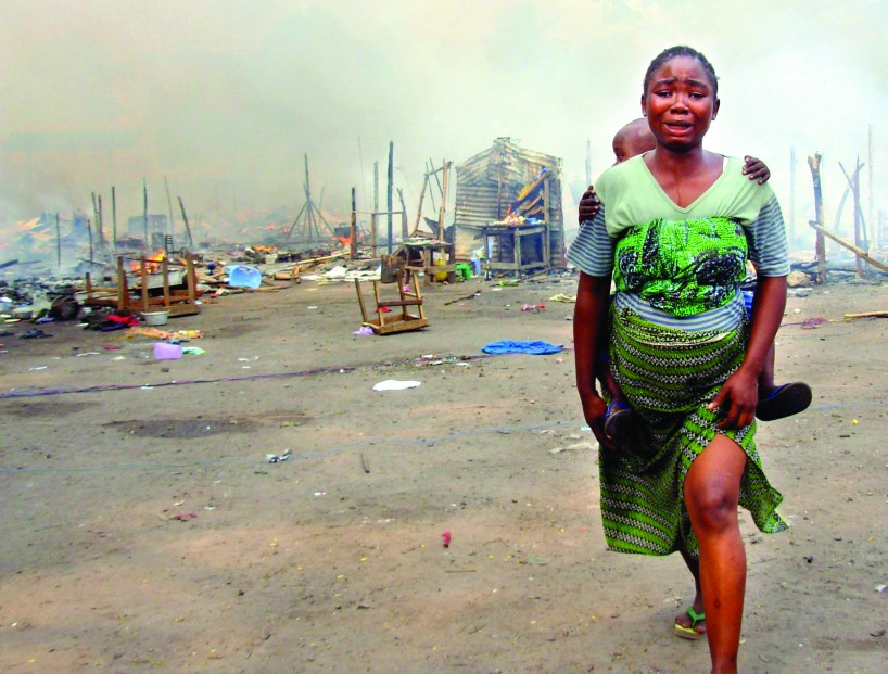 Woman and child run from burning compound of bodyguards of a presidential candidate, Kinshasa DRC.  Photo: Eddy Isango/IRIN