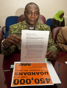 Canon Gideon Byamugisha with Avaaz campaign signatures and a petition calling for rejection of an anti-homosexuality bill. An Anglican priest with a parish outside of Kampala, he was the first religious leader in Africa to publicly announce that he was HIV positive. Photo: James Akena