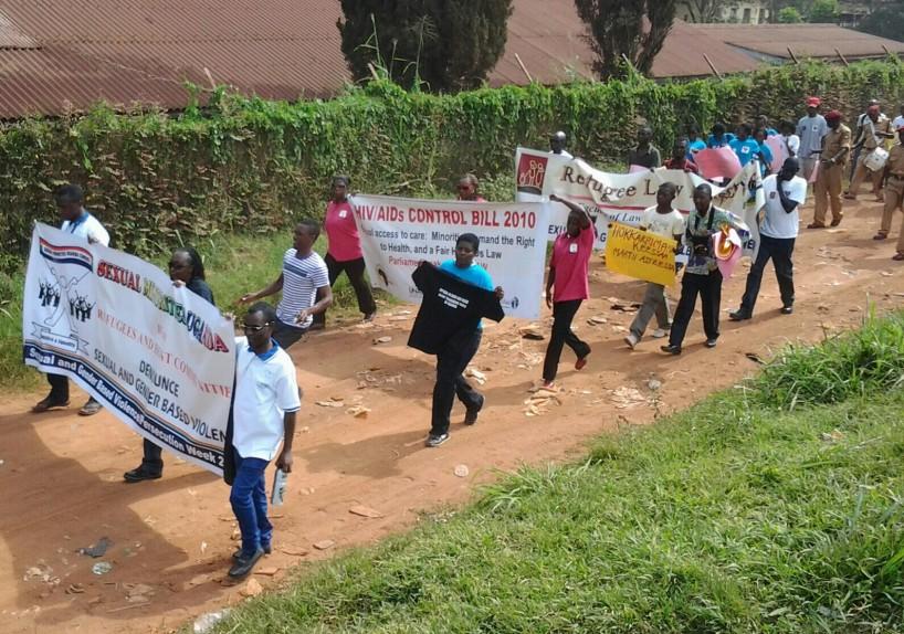 Une marche de soutien aux réfugiés, regroupant des organisations de défense des droits humains ougandaises, en 2013. On peut apercevoir la banderole de Sexual Minorities Uganda (SMUG), à gauche, qui dénonce la violence sexuelle et sexiste à l'égard des réfugiés. On estime qu'environ 400 000 réfugiés vivent en Ouganda.