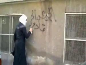 Une jeune révolutionnaire syrienne fait des graffitis sur les murs de Damas « l'armée syrienne libre arrive ».